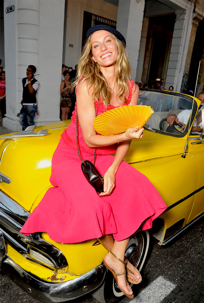 Supermodel Gisele Bundchen posing in front of one of the vintage taxis outside of the Chanel show
